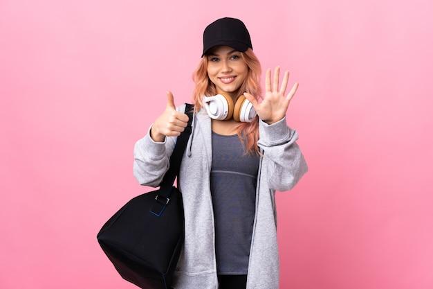 Sportfrau mit sporttasche, die sechs mit den fingern zählt