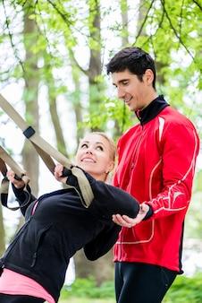 Sportfrau mit trainer am schlingentraining