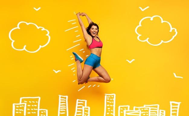 Sportfrau springt auf eine gelbe oberfläche fröhlicher und freudiger ausdruck