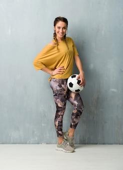Sportfrau über der schmutzwand, die einen fußball hält