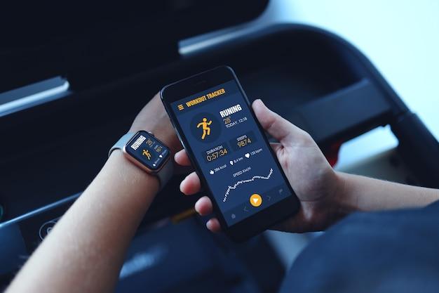 Sportfrauen, die ein laufband laufen lassen, verwenden eine smartwatch, verbinden die smartphone-trainings-app und hören musik. indoor-fitnessstudio-hintergrund. gesundheitssportkonzept