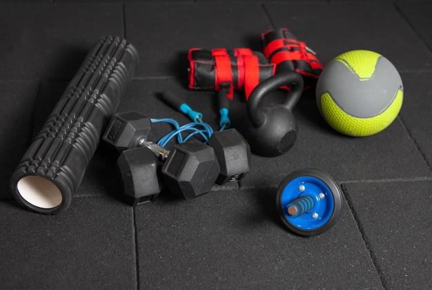 Sportgeräte für das funktionelle training. kettlebell und springseil, hanteln, medizinball, massagerolle, gewichte auf einem dunkelschwarzen boden. bodybuilding und fitness