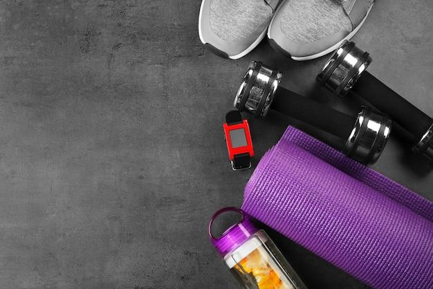 Sportgeräte und pulsuhr auf grauem hintergrund