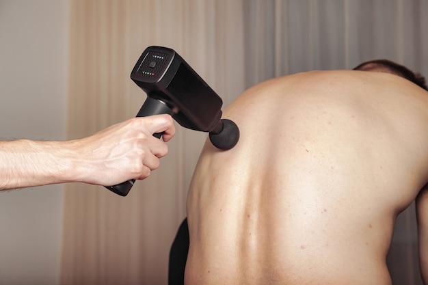 Sportgewehr-percussion-massage im medizinischen raum des fitnessstudios. masseur macht zu hause massageübungen
