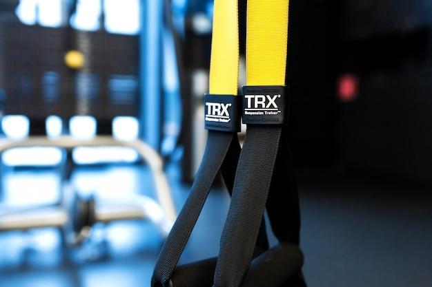 Sportgürtel, die zur gewichtsreduzierung beitragen. funktionelles trainingsgerät mit schwarzem und gelbem gurt. sportzubehör.