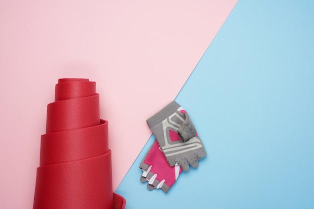 Sporthandschuhe und gedrehte rote neoprenmatte für yoga-sport auf rosa blauem hintergrund