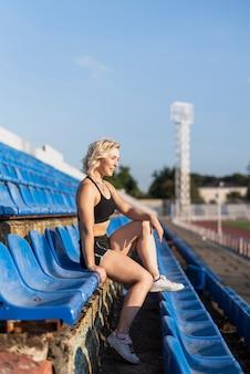 Sportive frau am stadionsitzen