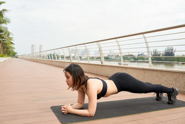 Sportive frau, die draußen plankenübung tut