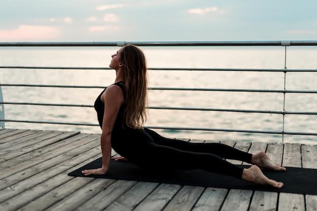Sportive frau, die morgens yoga asana auf dem meer tut