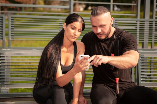 Sportive freunde, die mobile betrachten