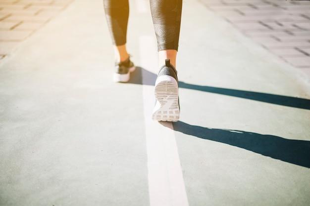 Sportive person der ernte, die auf bürgersteig läuft