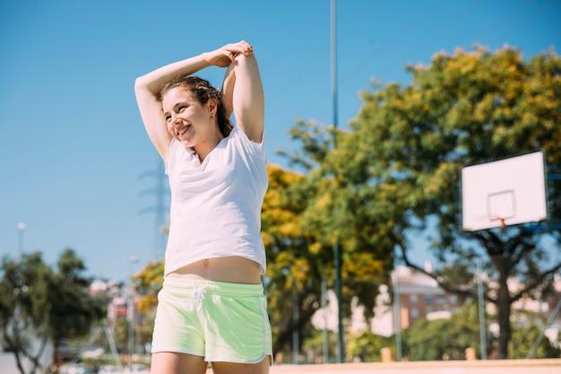 Sportiver begeisterter weiblicher jugendlicher, der draußen aufwärmt