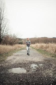 Sportiver junger mann, der auf schotterweg auf dem gebiet läuft
