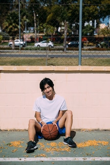 Sportiver junger mann, der draußen auf asphalt mit basketball sitzt
