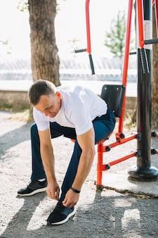 Sportiver mann binden schuhschnürsenkel