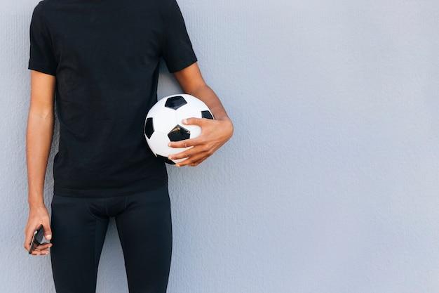Sportiver mann, der mit fußball und telefon steht