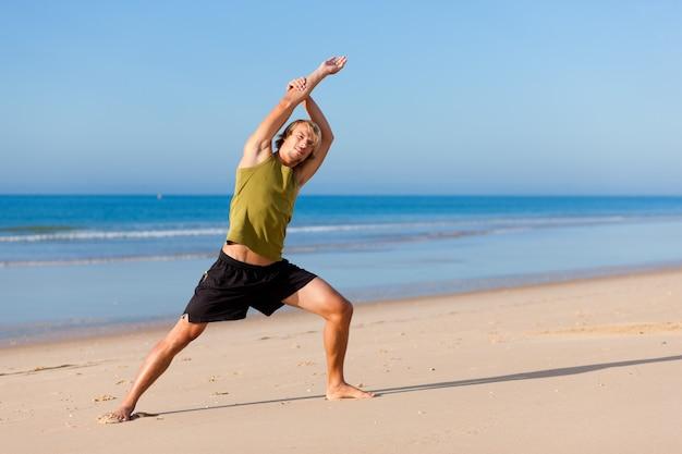 Sportiver mann macht gymnastik am strand