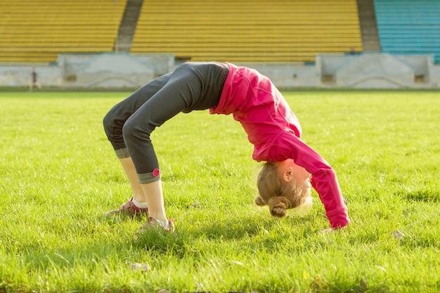 Sportives kleines mädchen, das auf grünem gras umgedreht steht