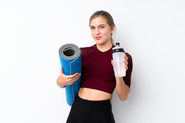 Sportjugendlichmädchen über weiß mit sportwasserflasche und mit einer matte