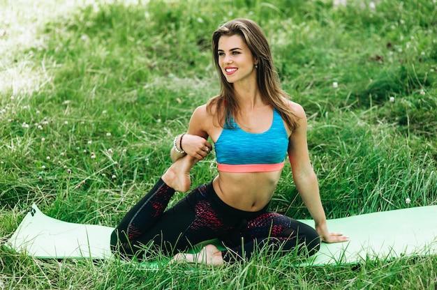 Sportkleidung des eignungssport-mädchens in mode, die yogaeignungsübung auf carimate im freien tut