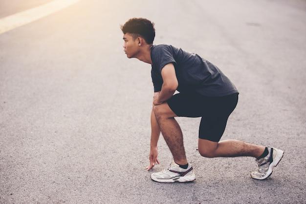 Sportkonzept, abschluss herauf den mann mit läufer auf der straße