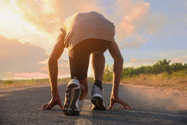Sportkonzept. der mann mit dem läufer auf der straße rennt zur übung. startlinie