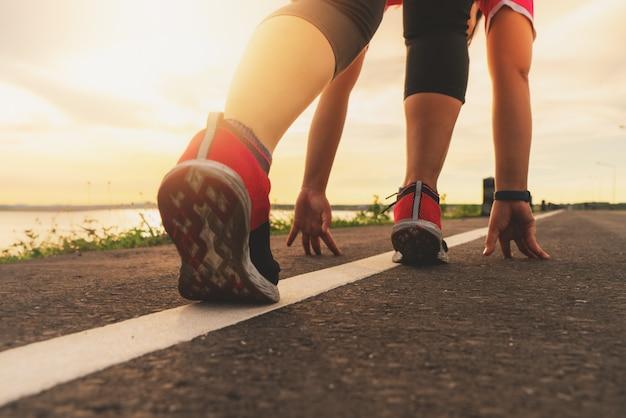 Sportläuferfüße, die auf sonnenuntergangsee laufen