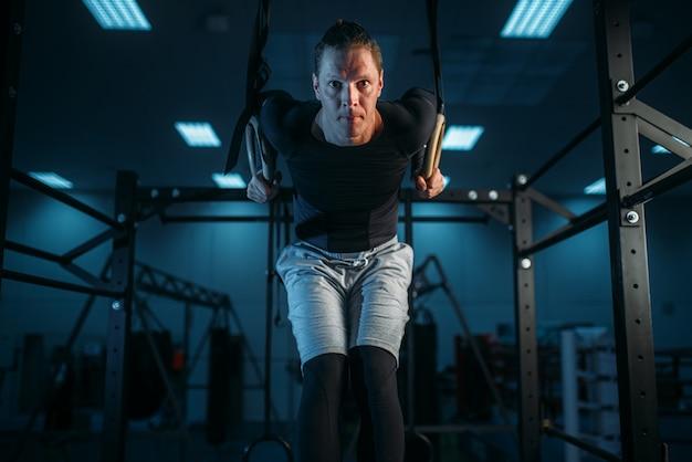 Sportler beim training, ausdauertraining an kardanischen ringen im fitnessstudio.