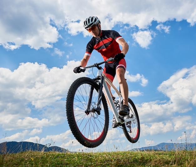 Sportler biker, der in der luft auf seinem fahrrad auf hellblauem himmel mit weißen wolken und entferntem hügelhintergrund fliegt