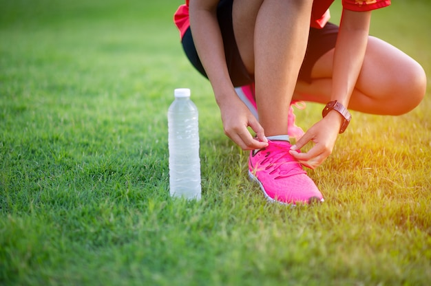 Sportler binden schuhe, bevor sie für eine gute gesundheit trainieren.