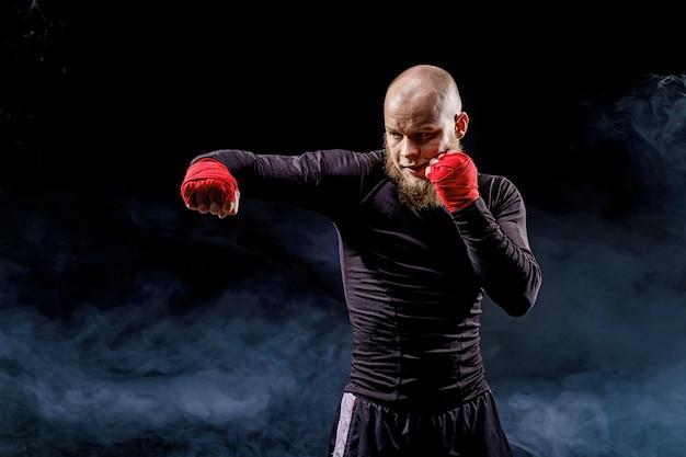 Sportler-boxer, der auf schwarzem hintergrund mit rauchboxen kämpft