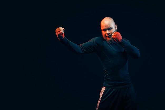 Sportler-boxer, der auf schwarzer wand kämpft