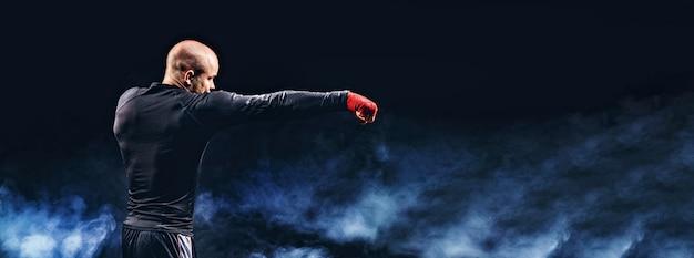 Sportler-boxer, der auf schwarzer wand mit rauch kämpft. boxsportkonzept