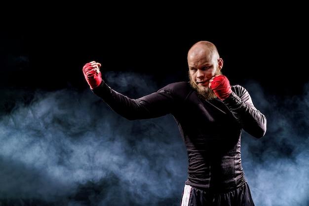 Sportler-boxer, der auf schwarzer wand mit rauch kämpft