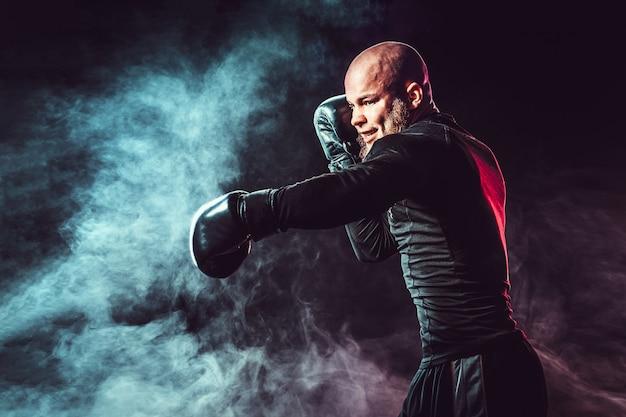 Sportler-boxer, der auf schwarzraum mit rauch kämpft