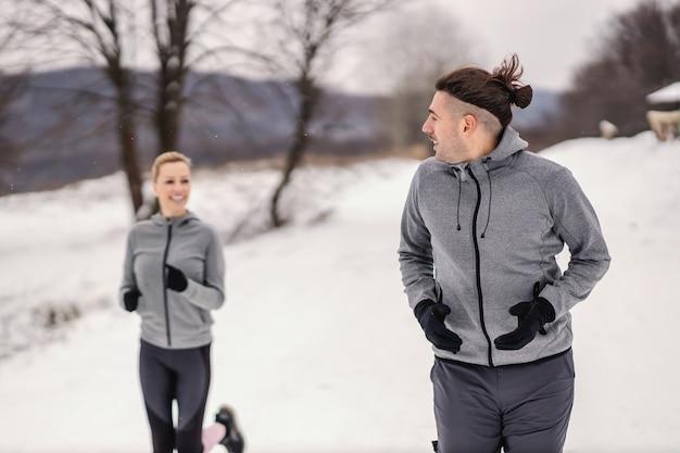 Sportler, der am verschneiten wintertag mit seinem freund in der natur läuft. winterfitness, gesundes leben, naturfitness