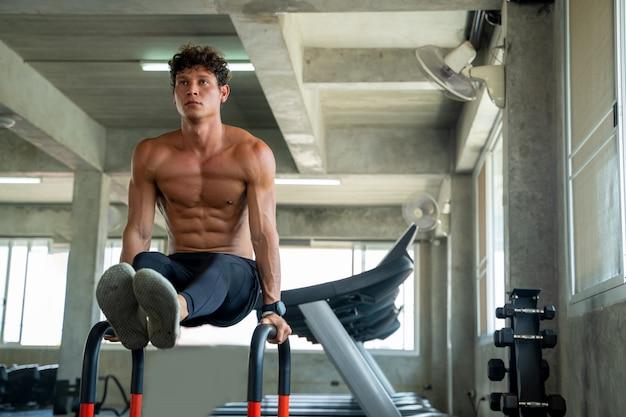 Sportler, der auf barren im fitnessstudio trainiert