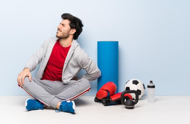 Sportler, der auf dem boden sitzt und unter rückenschmerzen leidet, weil er sich mühe gegeben hat