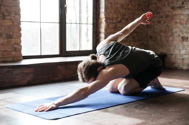 Sportler, der auf übungsmatte nach dem training im fitnessstudio streckt