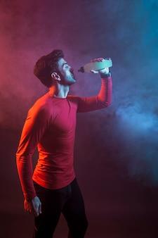 Sportler, der auffrischungswasser im studio trinkt