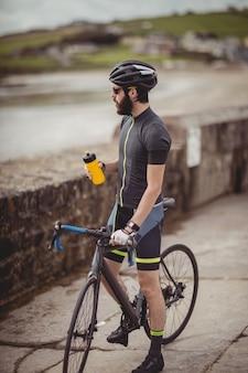 Sportler, der beim fahrradfahren von der flasche erfrischt