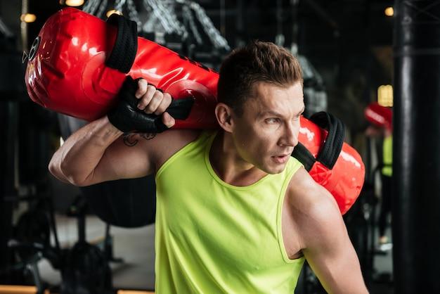 Sportler, der boxsack auf seiner schulter im fitnessstudio hält