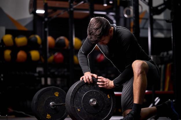 Sportler, der der langhantel das wechseln der schwarzen platten, ausrüstung für das krafttrainingskonzept hinzufügt. junger mann, der sportausrüstung für das training verwendet. allein im modernen fitnessstudio
