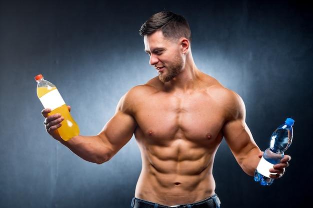 Sportler, der eine flasche wasser und soda hält.