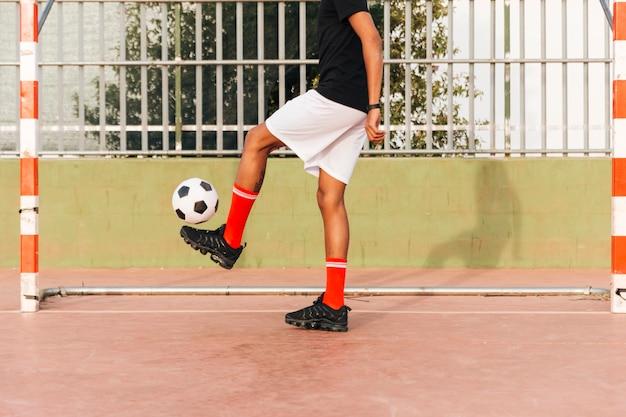 Sportler, der fußball am stadion tritt
