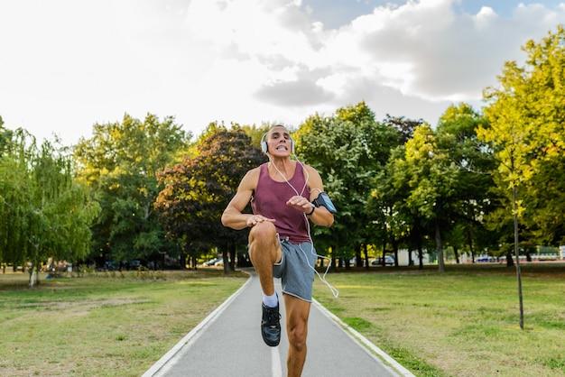 Sportler, der im wald rüttelt. gesunder lebensstil hübscher mann, im park rüttelnd, tragende kopfhörer, hörende musik.