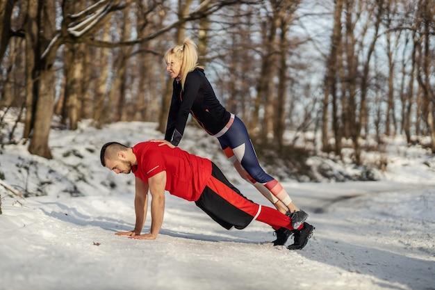 Sportler, der im winter liegestütze macht, während sportlerin in seinem rücken steht