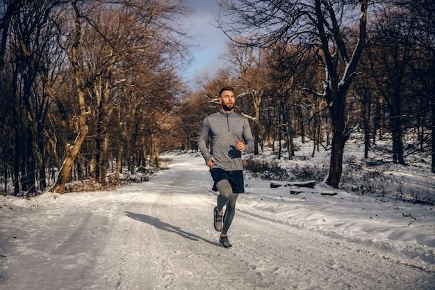 Sportler, der in der natur auf schnee im winter joggt. winter fitness, fitness in der natur, kühles wetter