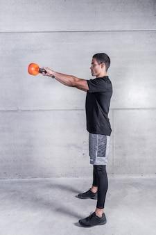 Sportler, der kettlebellschwingen tut
