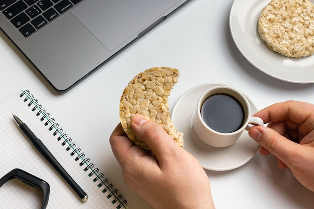 Sportler, der knusperige reisrunden mit erdnüssen, tasse kaffee nahe dem laptop isst